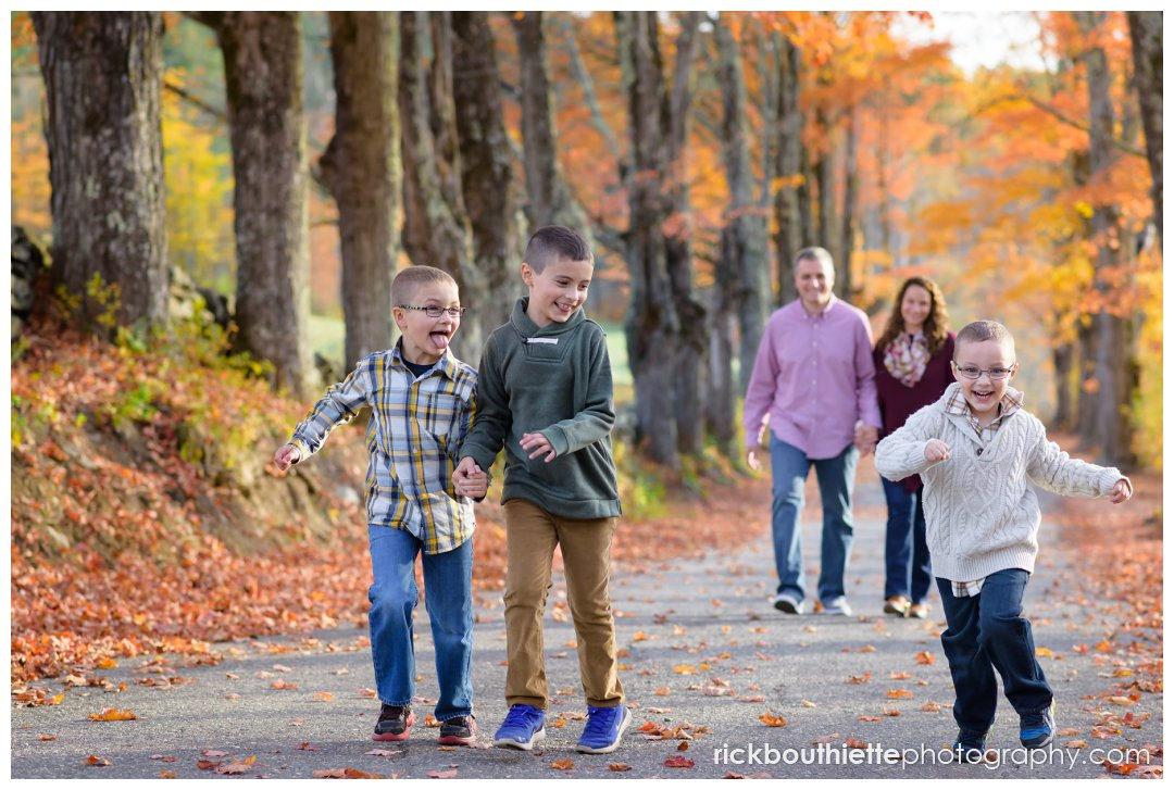 family portrait photography - three boys running with parents in background