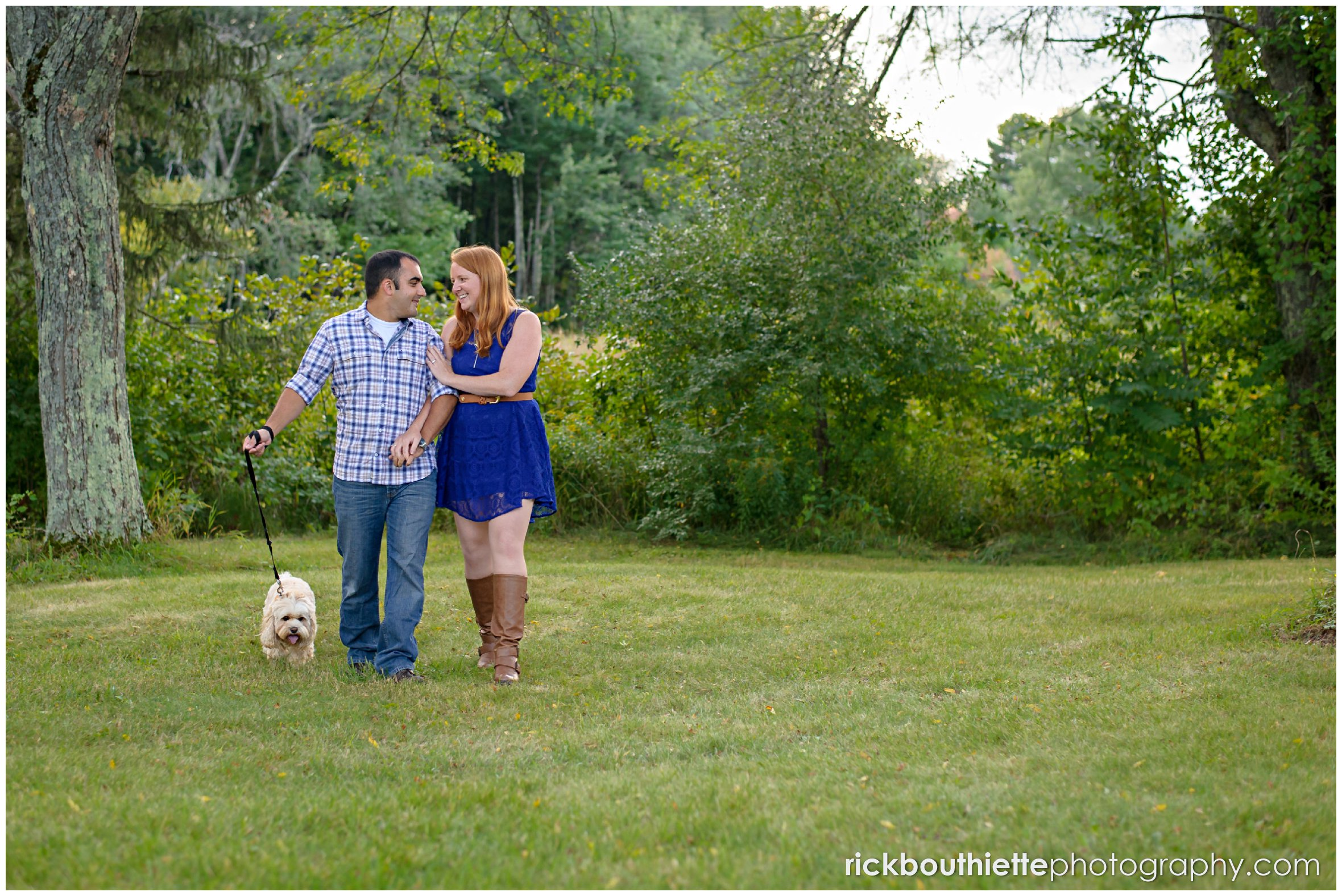 couple walking with their dog during NH engagement session
