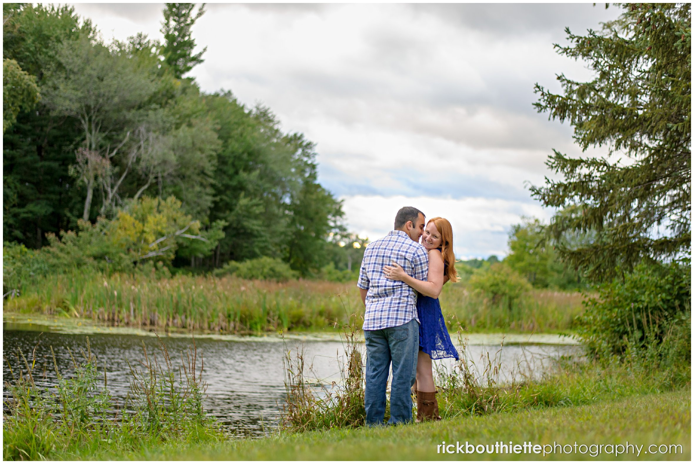 couple kissing by the water at engagement session