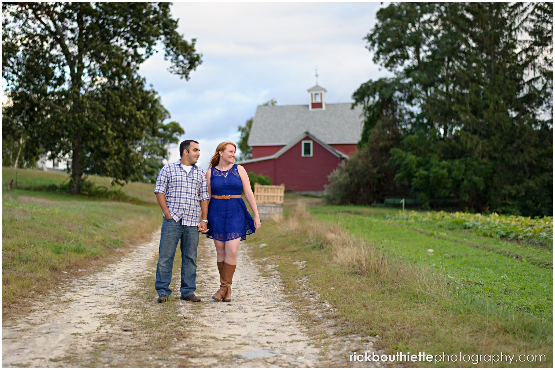 couple walking down road with red barn in background during engagement session