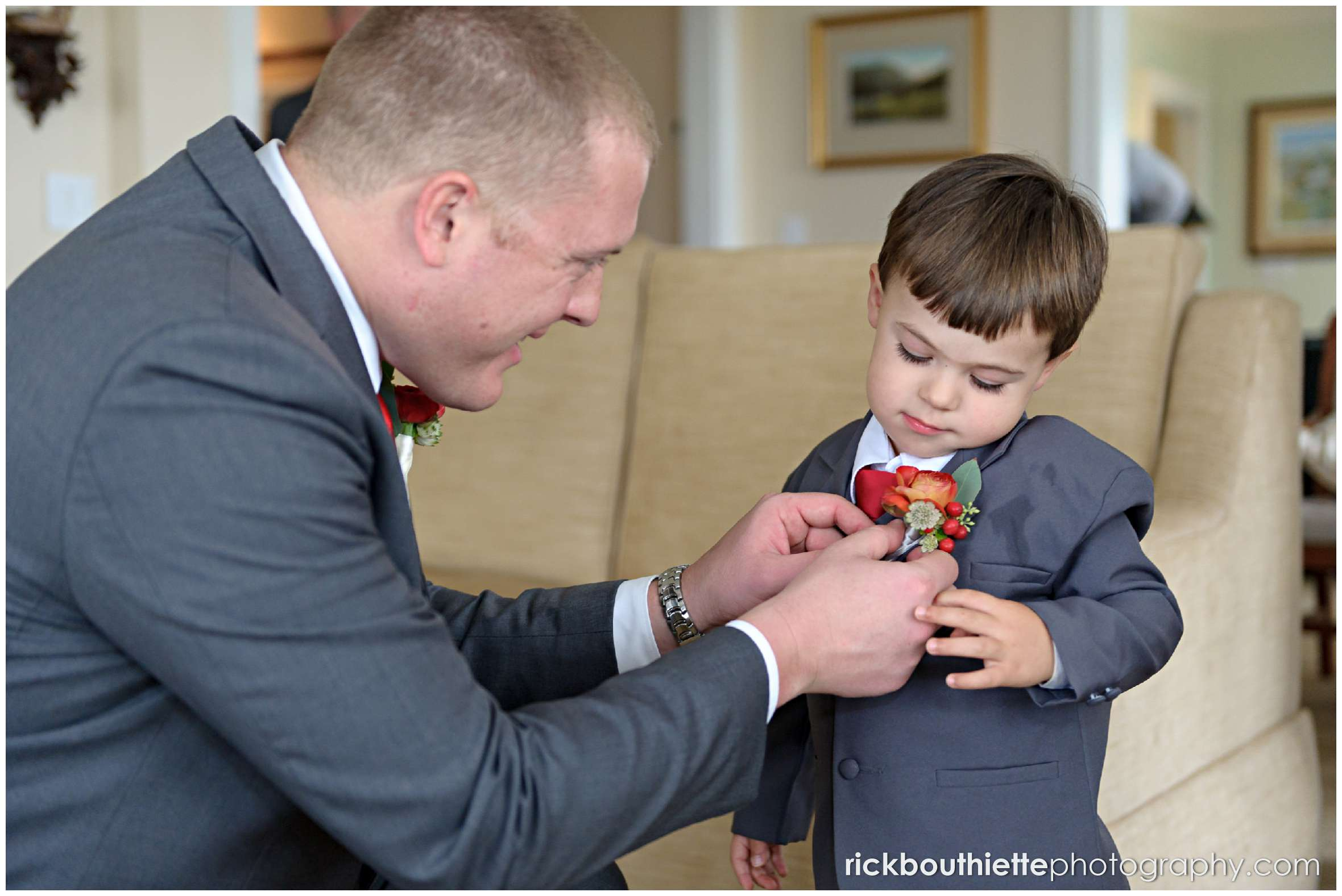 groom pinning boutonniere on ring bearee