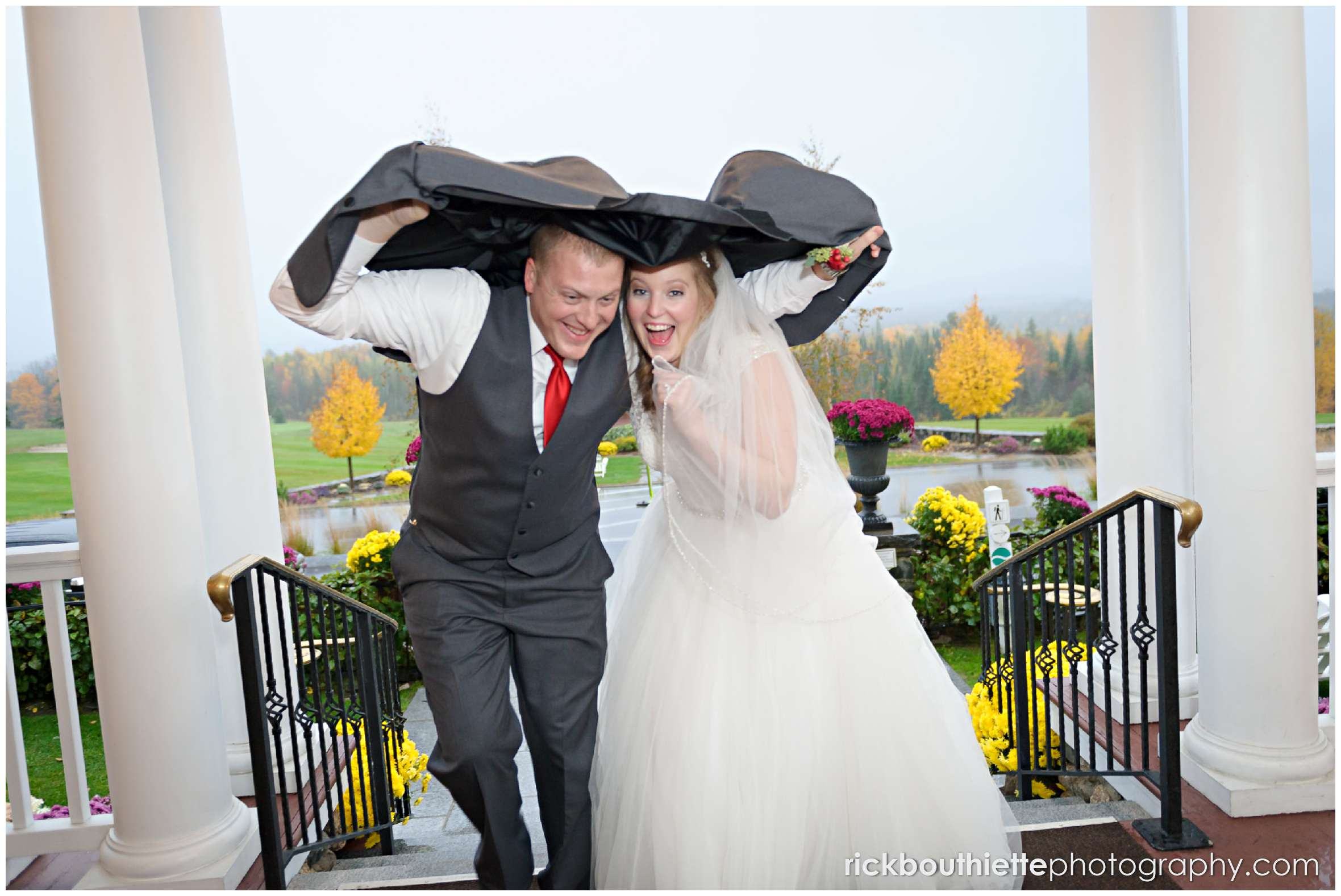 bride and groom running up stairs with jacket overhead in rain