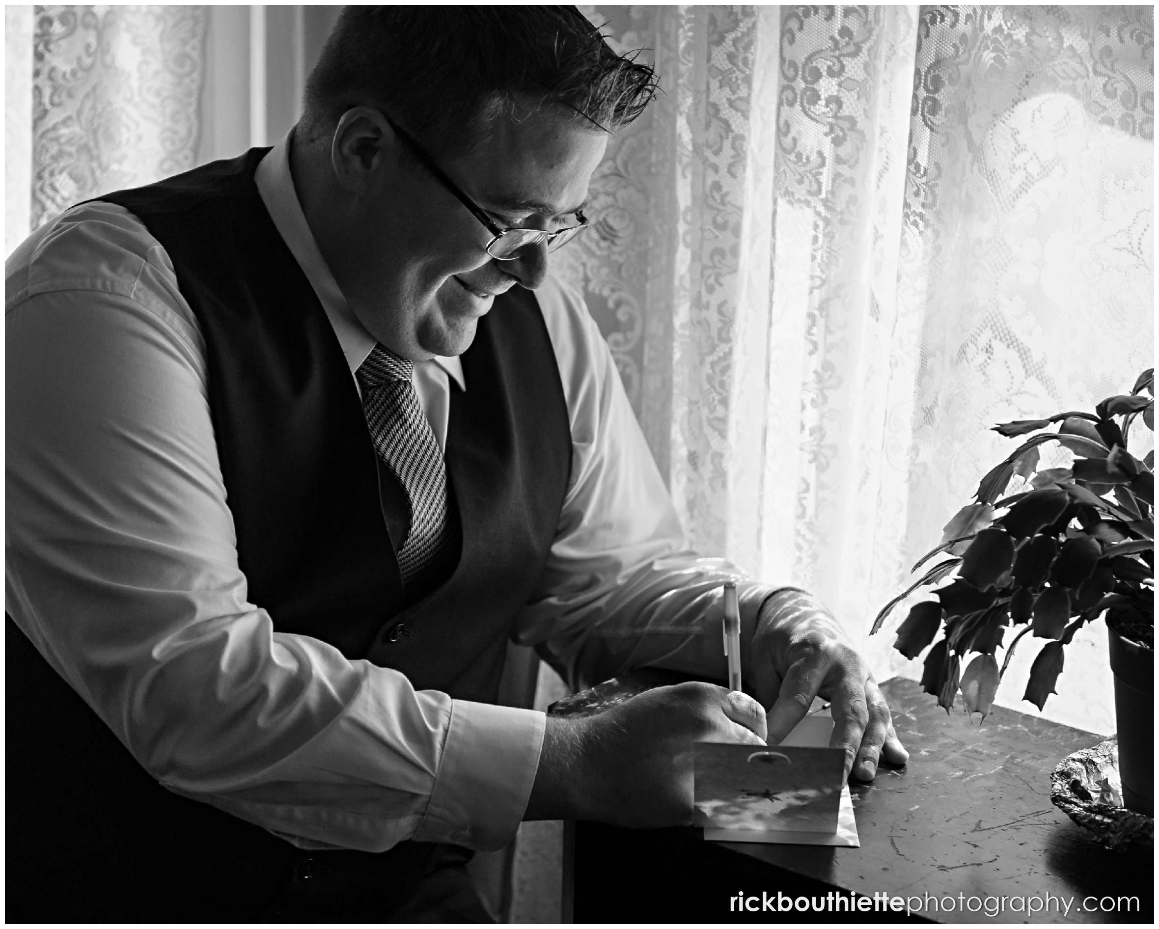 black & white of groom writing a letter to his bride to be