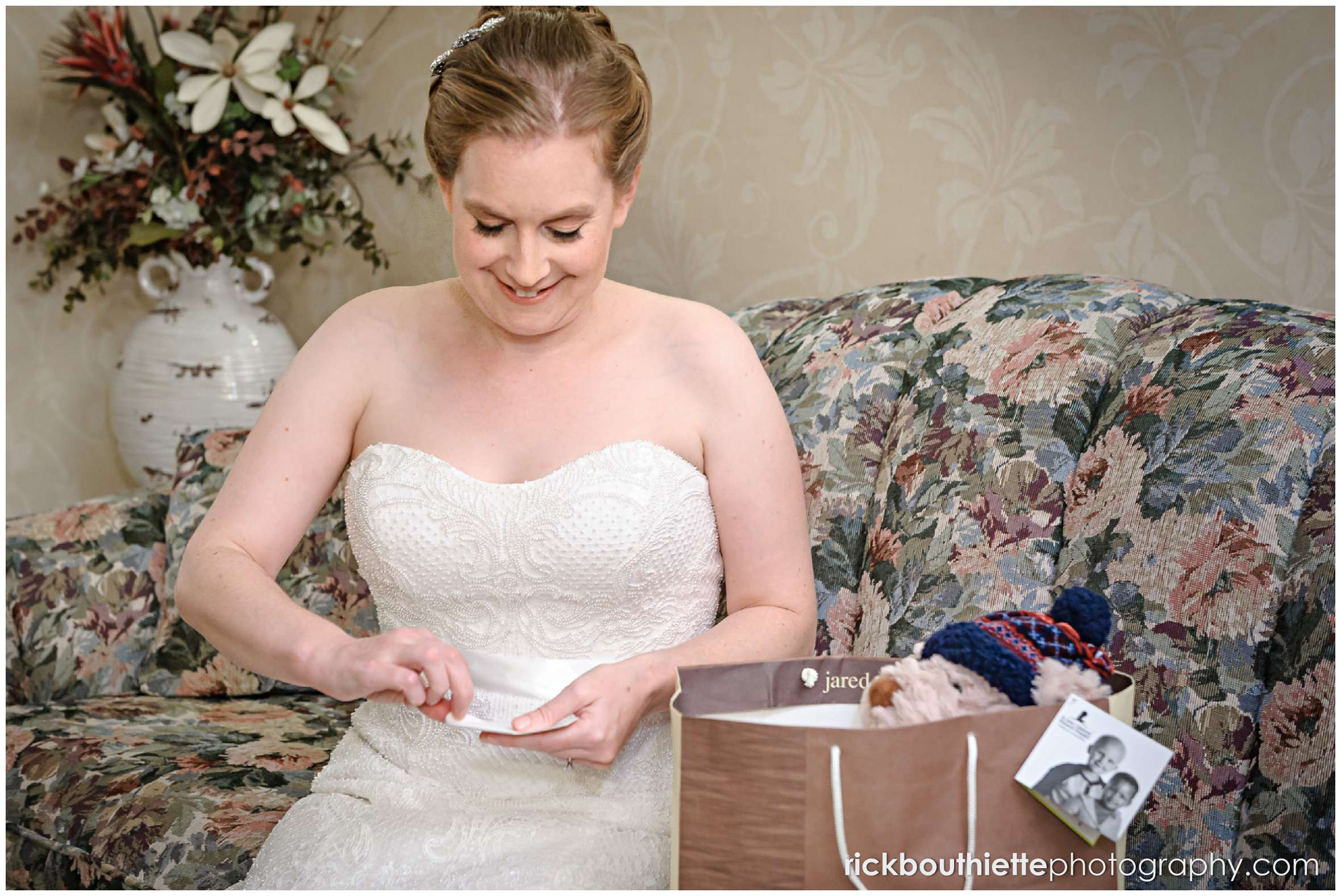 bride opening a card and gift from her husband to be before her seacoast wedding