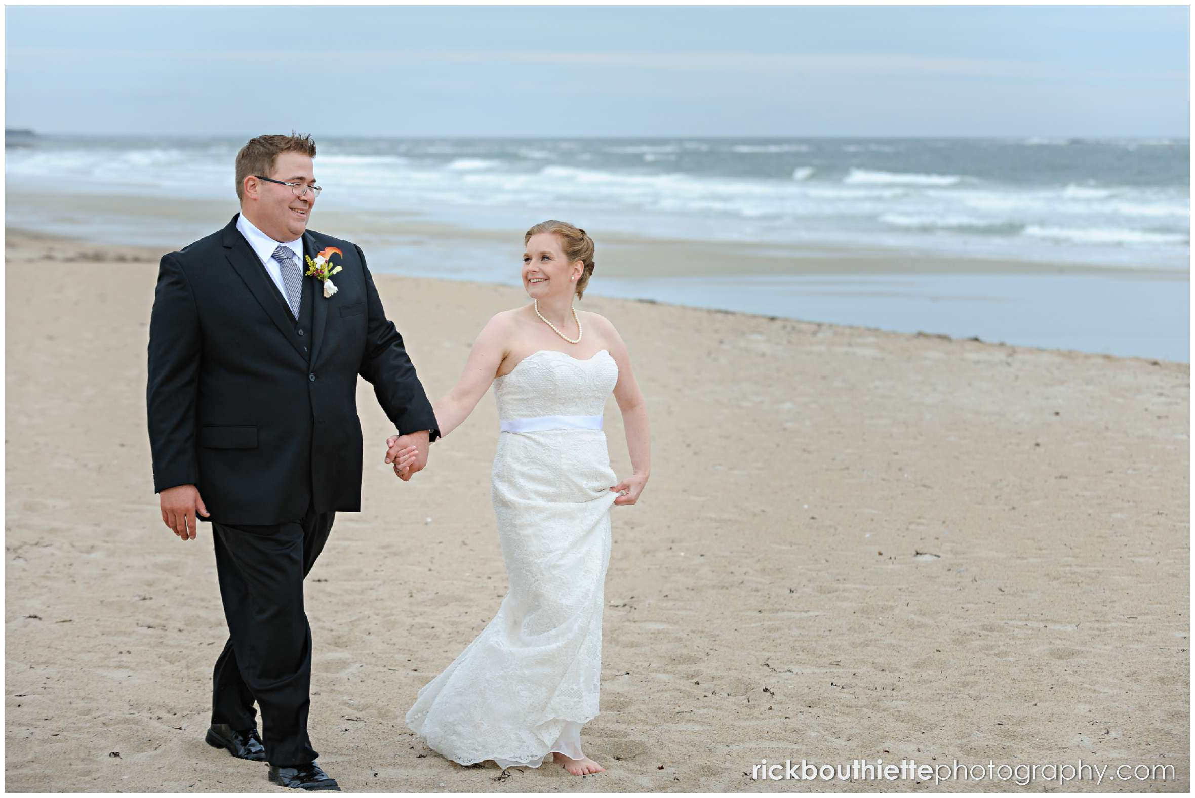 bride and groom walking on Seabrook beach after their seacoast wedding ceremony