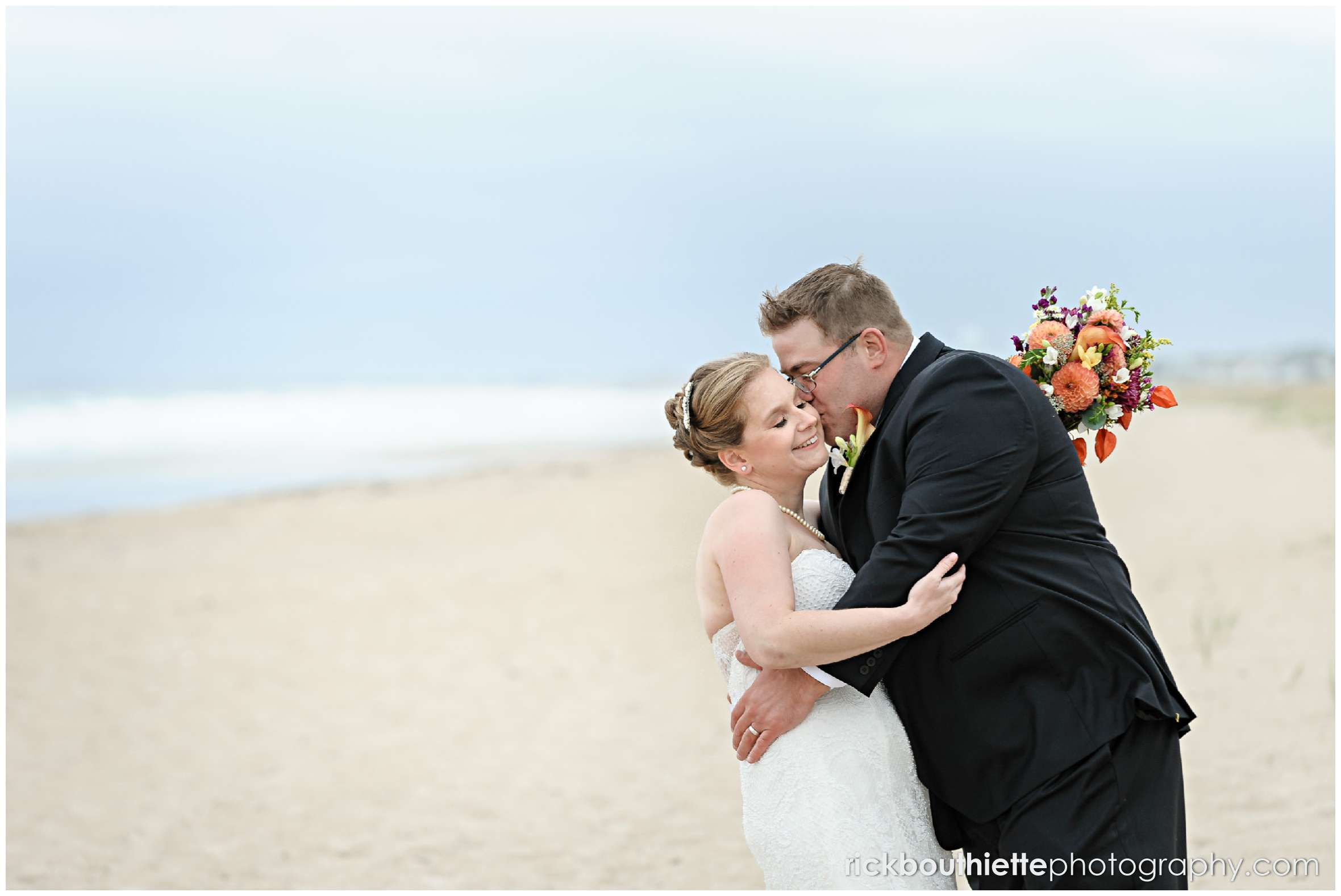 bride and groom kiss on Seabrook beach after their seacoast wedding ceremony