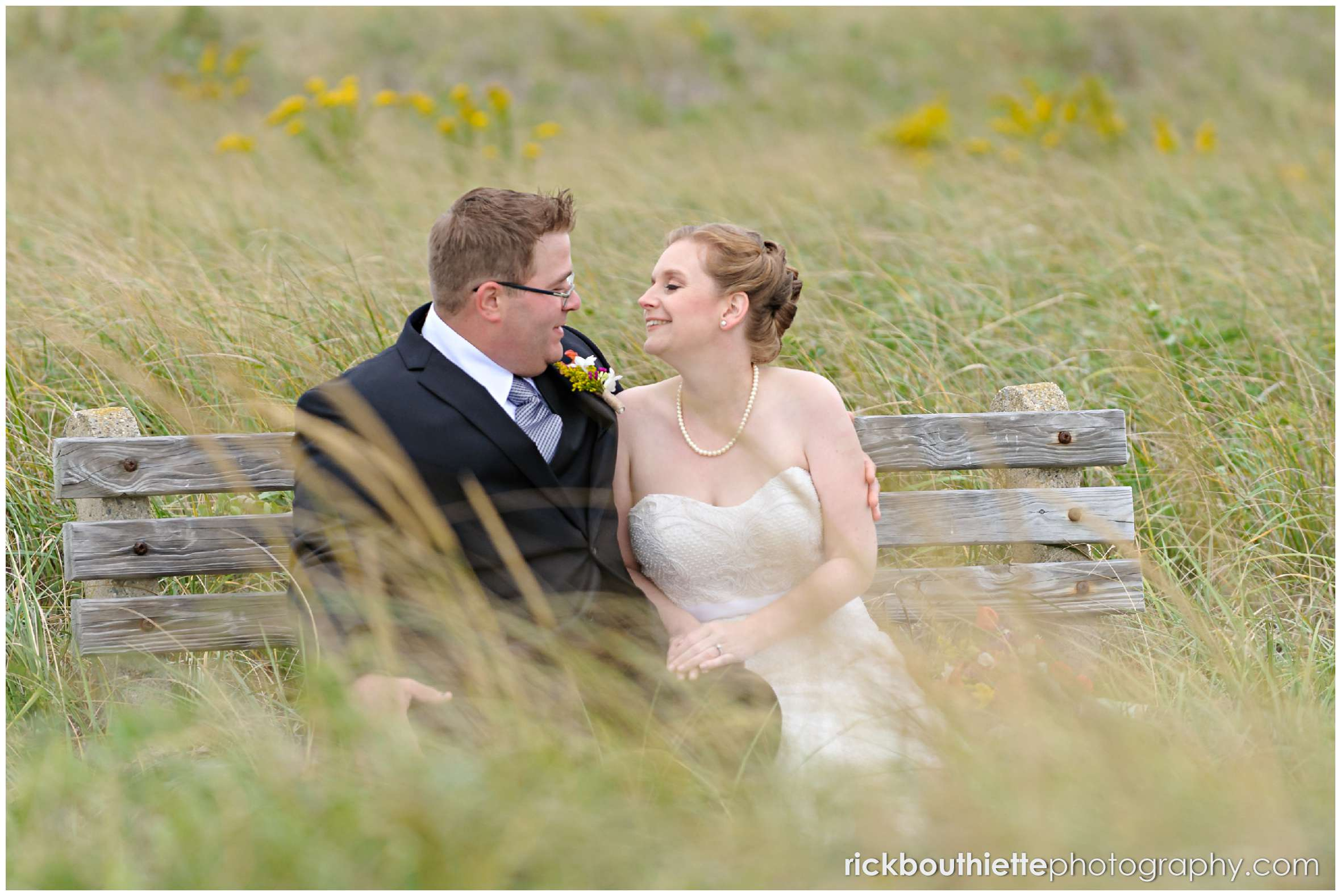 bride and groom sitting on a bench on Seabrook beach after their seacoast wedding ceremony