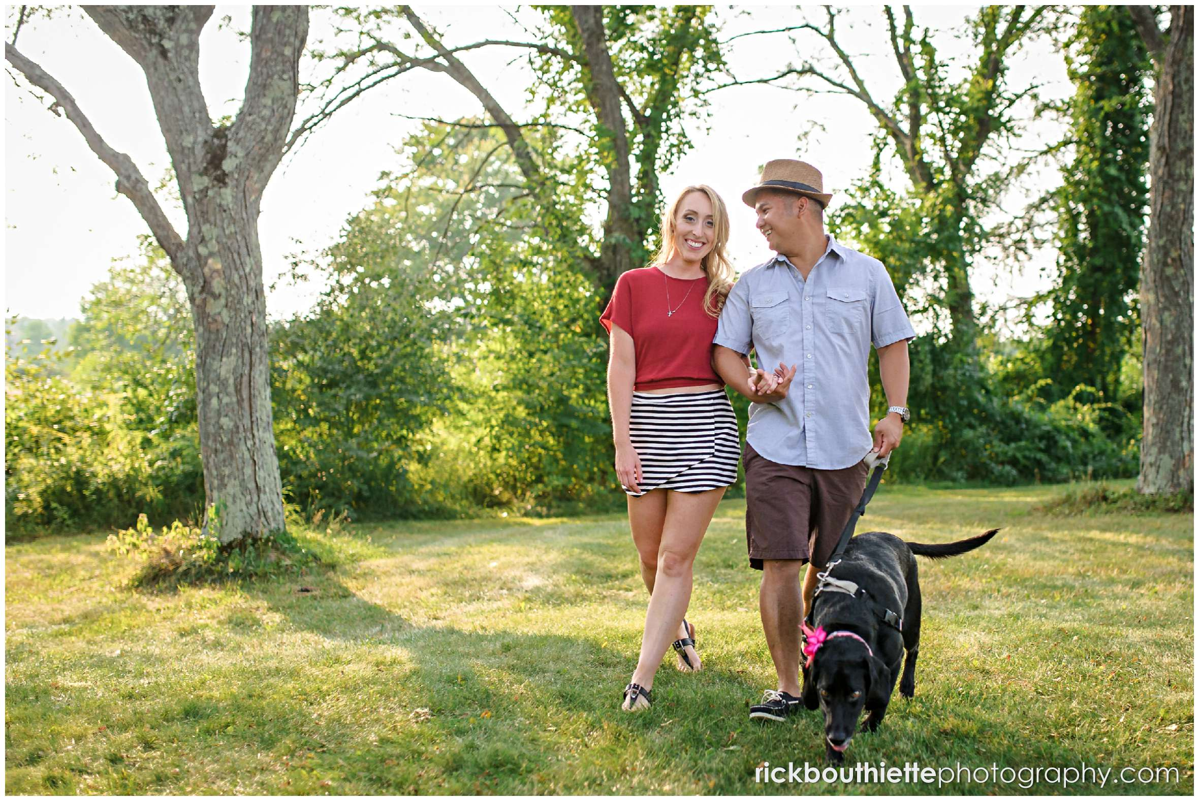 couple walking with their dog during New Hampshire apple orchard engagement session