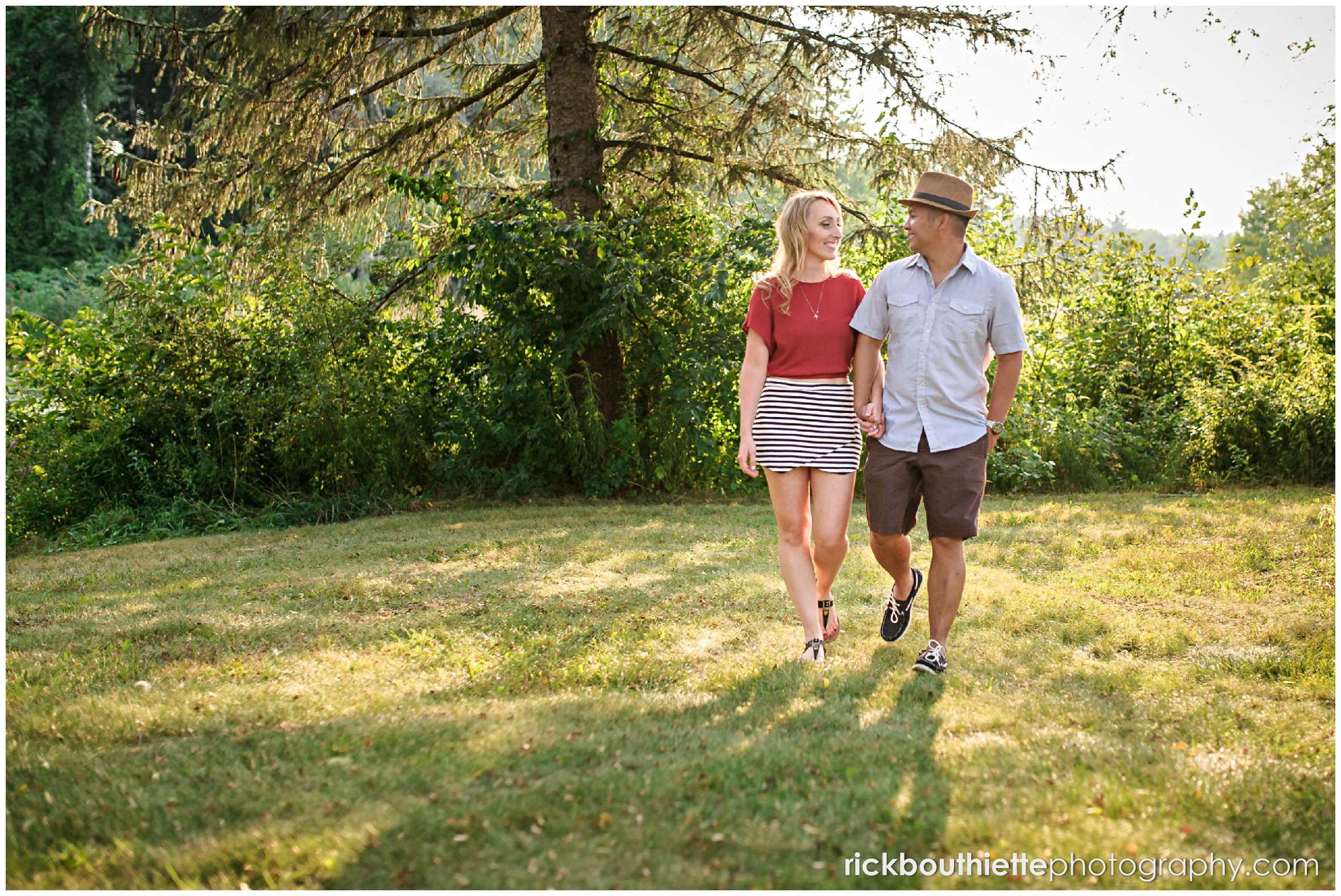 couple walking while holding hands during New Hampshire apple orchard engagement session