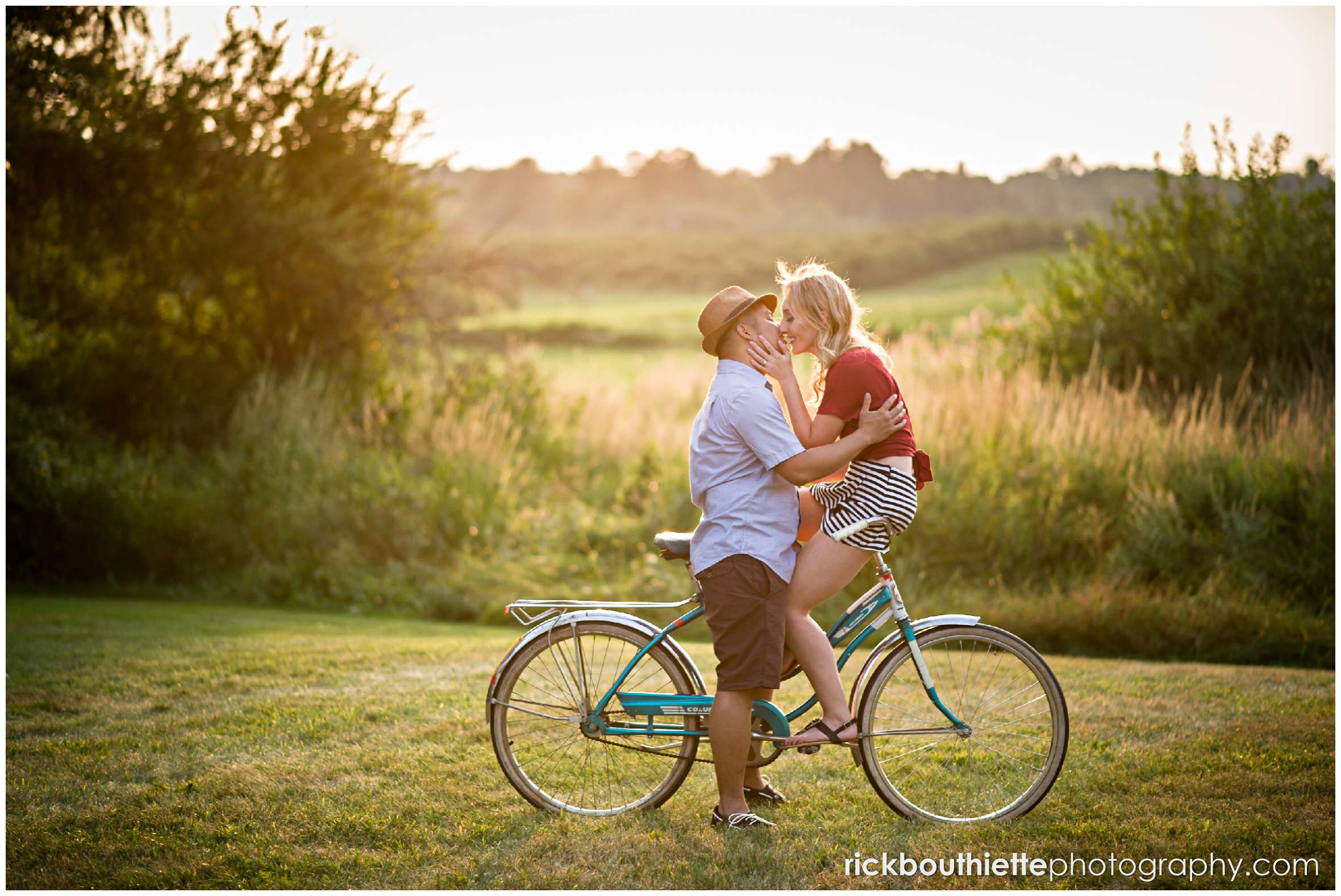 couple on vintage bicycle as the sun sets at their New Hampshire apple orchard engagement session