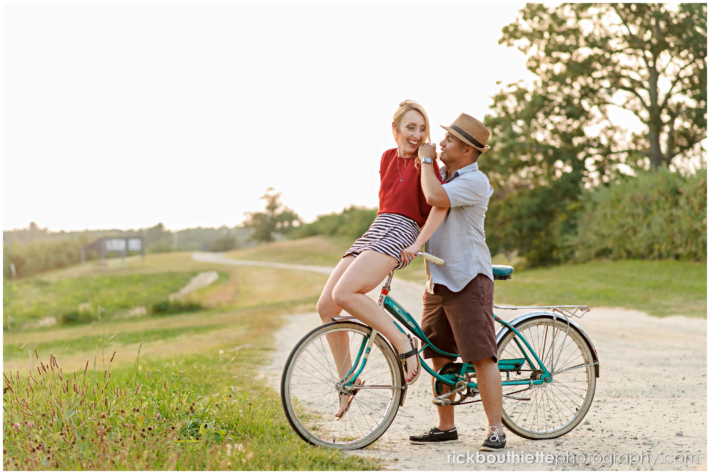 couple with vintage bicycle on dirt road at apple orchard engagement session