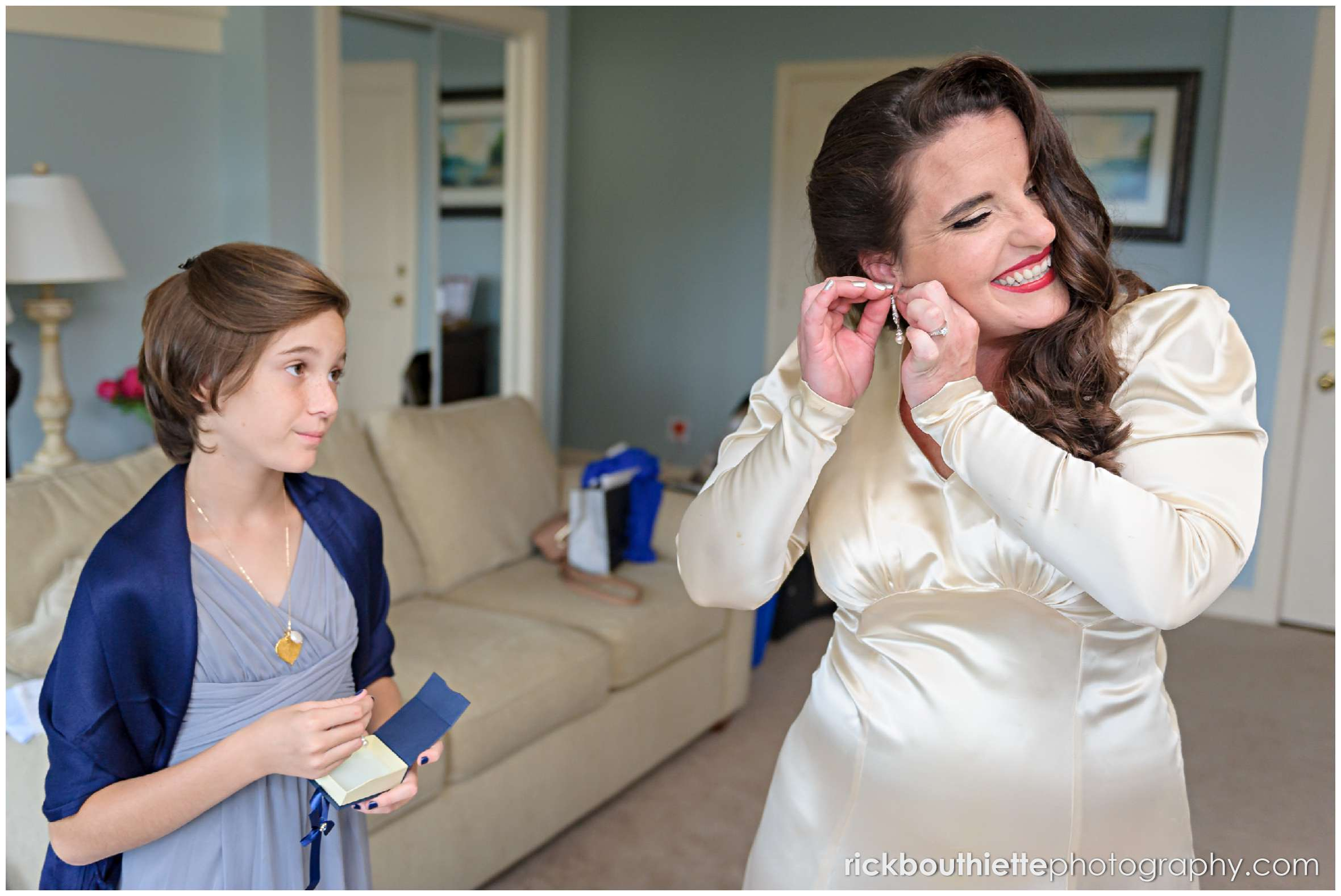 bride putting her earrings on with help of a bridesmaid