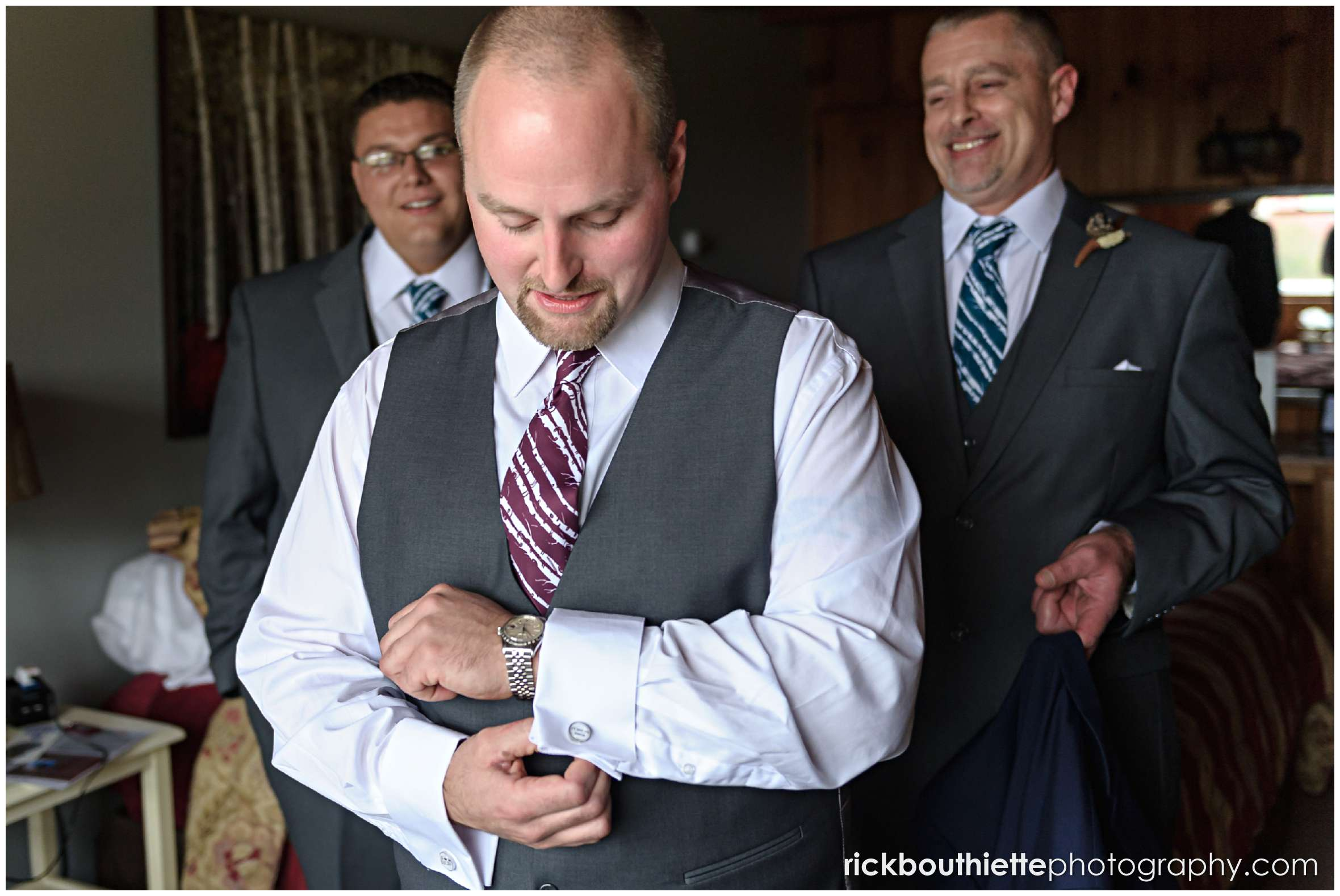 groom adjusting his cuff links with groomsmen looking on as he gets ready for his Snowvillage Inn wedding